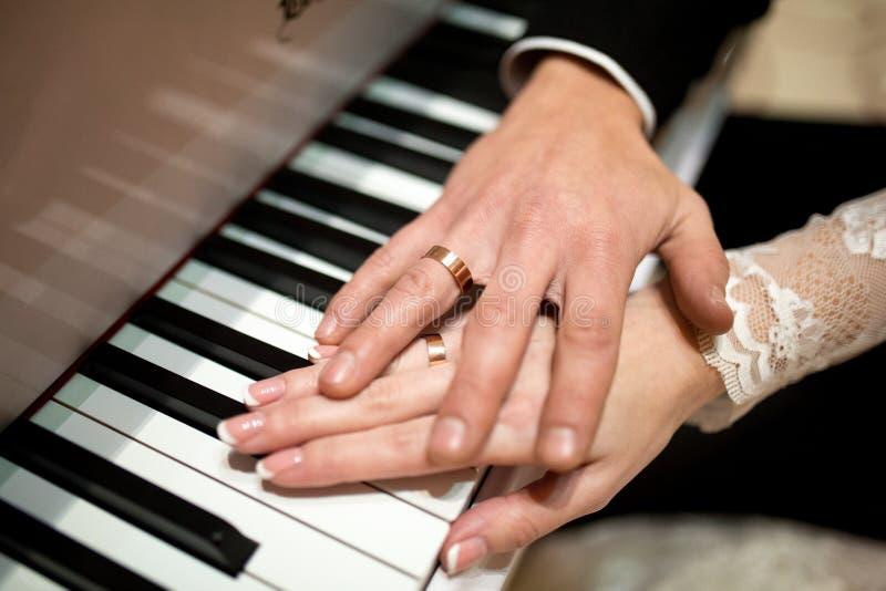 Huwelijk Twee handen op pianosleutels royalty-vrije stock afbeeldingen