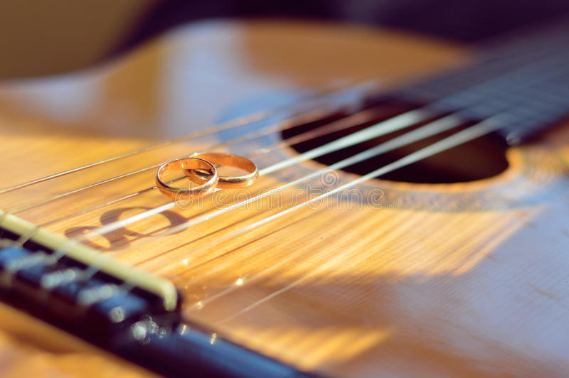 Huwelijks gouden ringen op gitaarkoorden royalty-vrije stock afbeelding