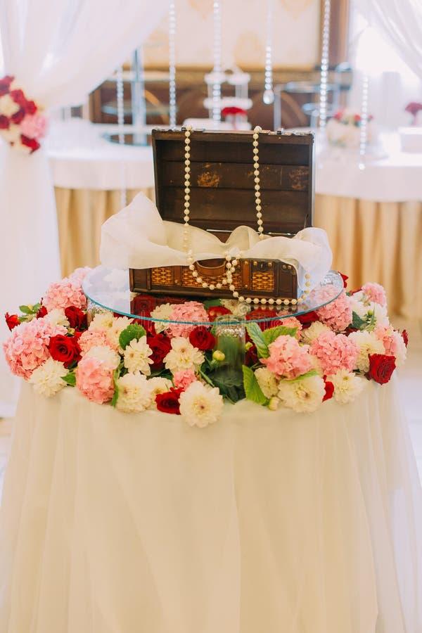 Huwelijks houten die vakje met parels wordt verfraaid op de lijst worden geplaatst met kleurrijke bloemen wordt behandeld royalty-vrije stock afbeelding