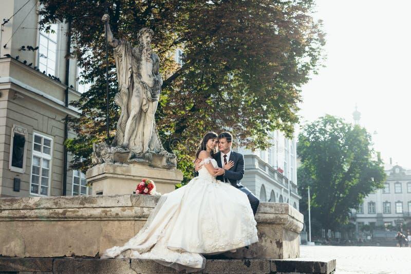Huwelijks openluchtportret Het houden van handen enkel echtpaar zit op de oude fontein stock foto's