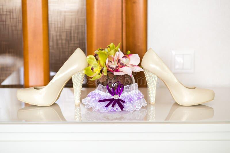 Huwelijks witte bruids kouseband, schoenen en bloemen bij de achtergrond stock foto