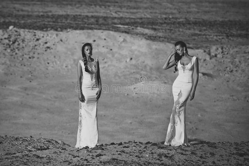 Huwelijksagentschap Twee meisjes in witte kleding die in zandduinen stellen stock foto's