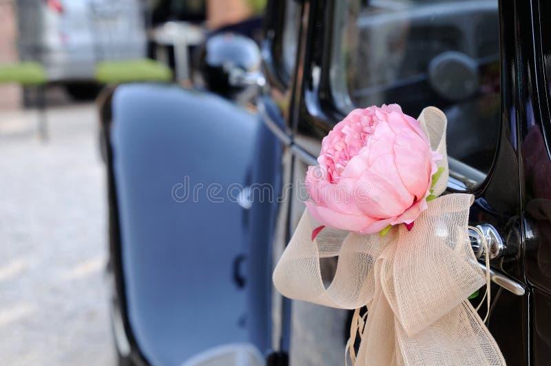Huwelijksauto met bloem en witte boog achtermening royalty-vrije stock afbeelding