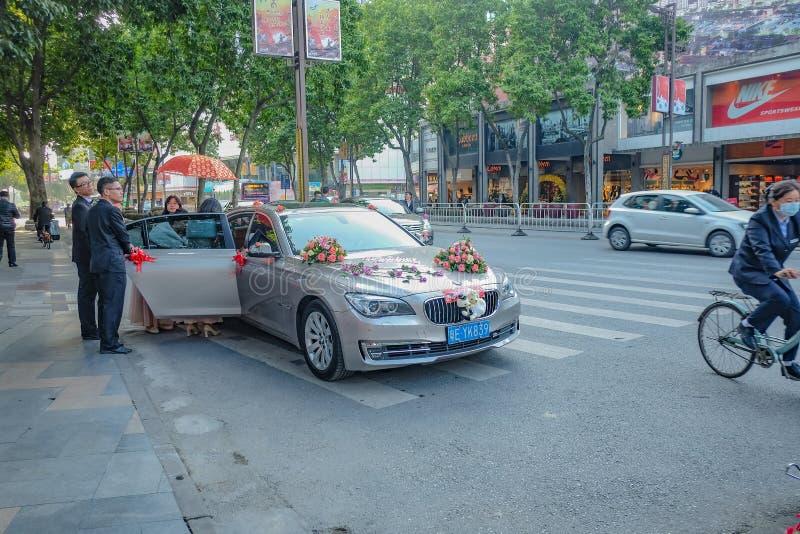 Huwelijksauto met bruidsmeisje en groomsman de stad China van Foshan stock afbeelding