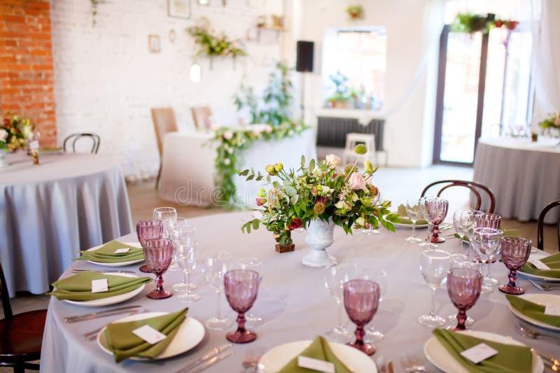 Huwelijksbanket, gediende lijsten met bloemen en veel groen royalty-vrije stock fotografie