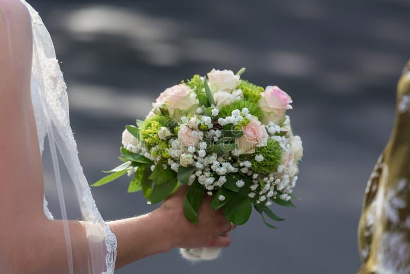 Huwelijksbloemen in bruidenhand stock foto