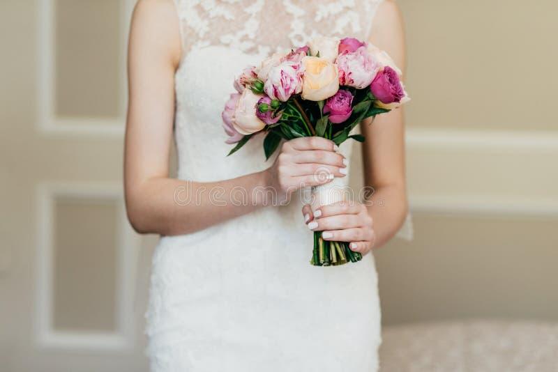 Huwelijksboeket in bruid` s handen Slanke bruid die in witte kleding mooie bloemen in handen houden die, die gaan huwen, op haar  royalty-vrije stock fotografie
