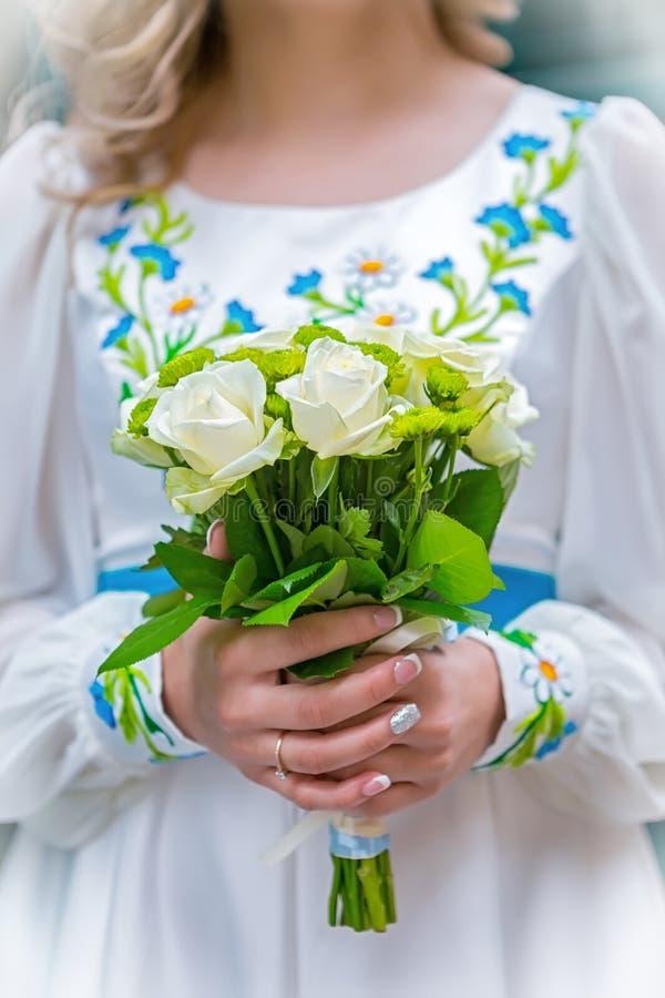 Huwelijksboeket in de handen van de bruid in de nationale Oekraïense kleding stock afbeelding