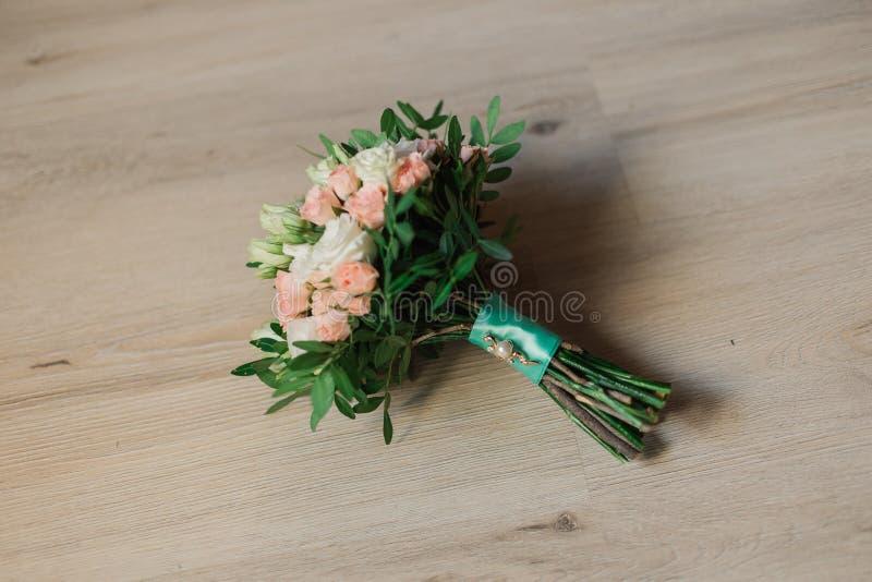Huwelijksboeket die op grijs tapijt tijdens voorbereiding vóór viering liggen Zijaanzicht van decoratieve roze bloemen en royalty-vrije stock fotografie