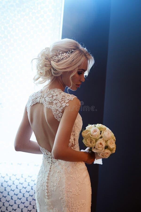 Huwelijksboeket in mand Een vrouw in een witte huwelijkskleding die een boeket van bloemen in haar handen houden Mooi blondemeisj royalty-vrije stock afbeelding