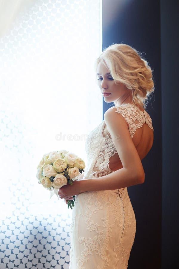 Huwelijksboeket in mand Een vrouw in een witte huwelijkskleding die een boeket van bloemen in haar handen houden Mooi blondemeisj royalty-vrije stock afbeeldingen
