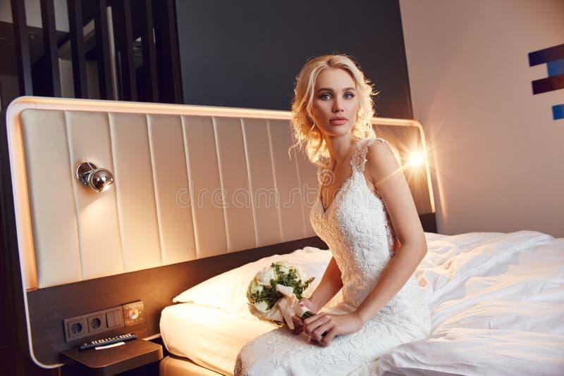 Huwelijksboeket in mand Een vrouw in een witte huwelijkskleding die een boeket van bloemen in haar handen houden Mooi blondemeisj stock afbeeldingen