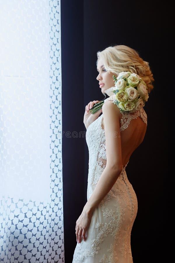 Huwelijksboeket in mand Een vrouw in een witte huwelijkskleding die een boeket van bloemen in haar handen houden Mooi blondemeisj royalty-vrije stock foto