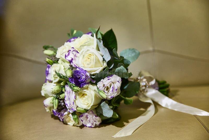 Huwelijksboeket met linten Rozen, fresia Beige achtergrond stock fotografie