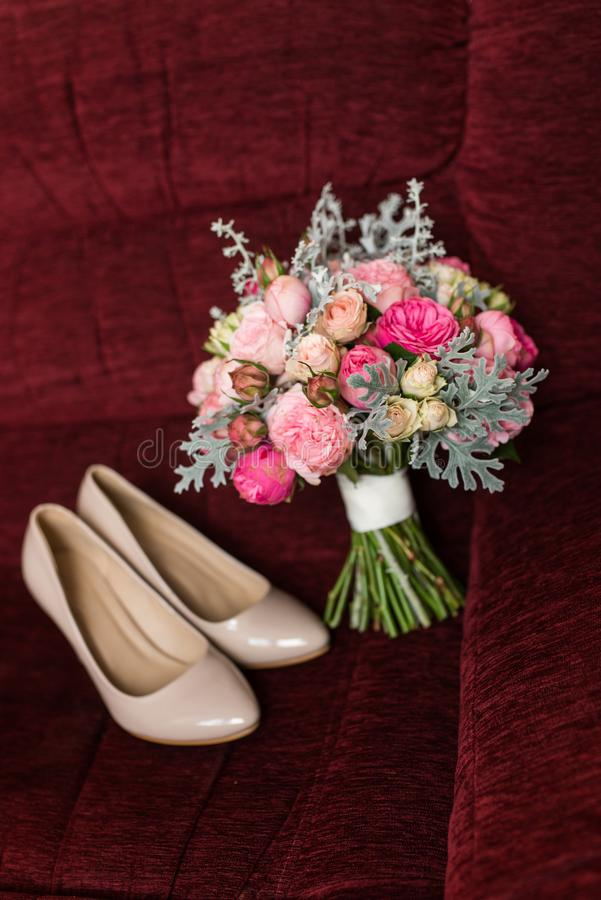 Huwelijksboeket met purpere en roze rozen die op een rode leunstoel liggen Beige bruids schoenen uit nadruk stock foto