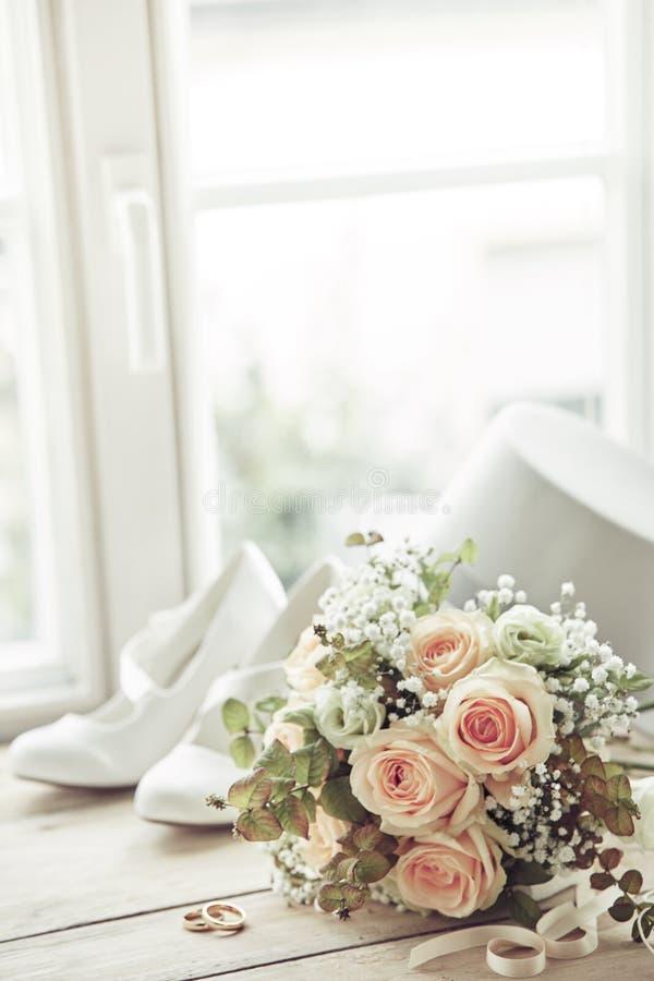 Huwelijksboeket, ringen en witte schoenen royalty-vrije stock fotografie