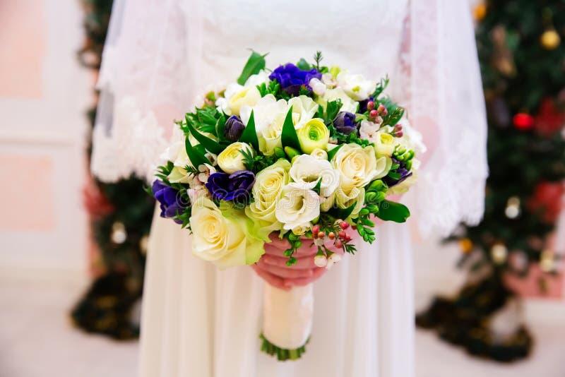 Huwelijksboeket van bloemen in bruidenhanden stock afbeeldingen