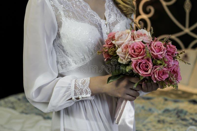 Huwelijksboeket van roze rozen in de handen van de verzamelende bruid stock afbeelding
