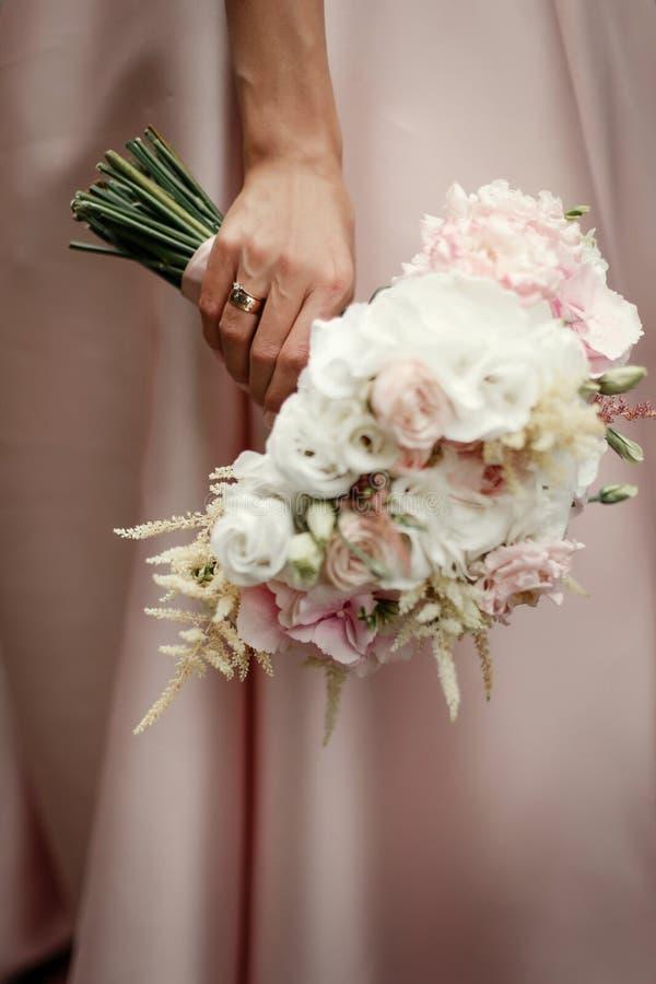 Huwelijksboeket van roze rozen en witte bloemen bruidholding i royalty-vrije stock fotografie