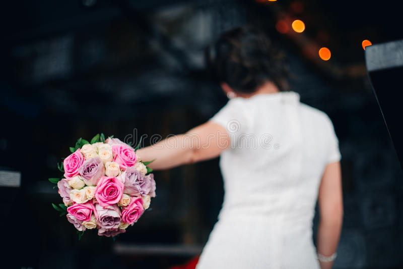 Huwelijksboeket van roze, violette en witte rozen Terug van de bruid in bokeh stock foto's
