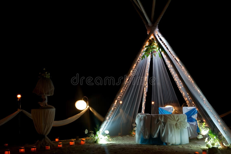 Huwelijksboog en opstelling met bloemen op strand bij nacht stock afbeeldingen