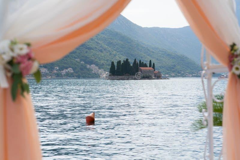 Huwelijksboog met bloemen en doek voor de ceremonie dichtbij het overzees wordt verfraaid die royalty-vrije stock fotografie