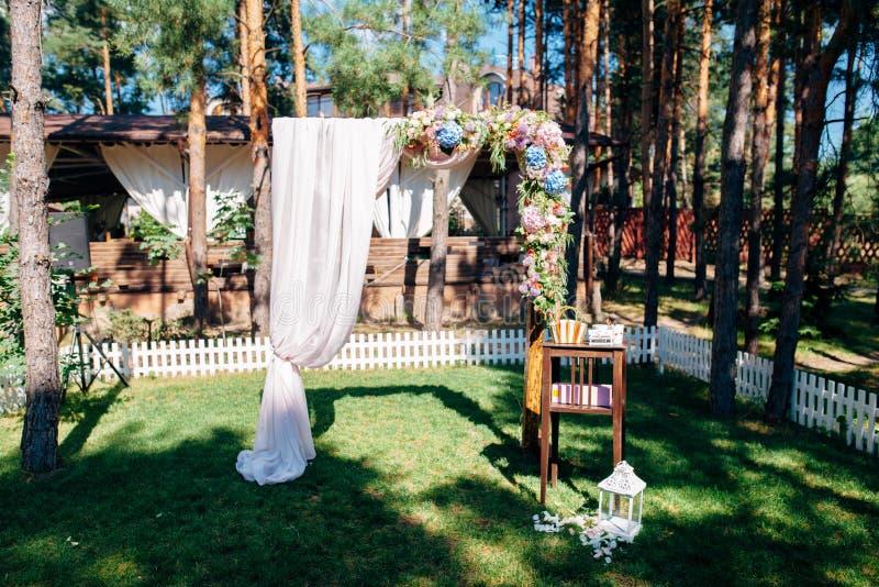 Huwelijksboog met bloemen in het bos wordt verfraaid dat stock fotografie