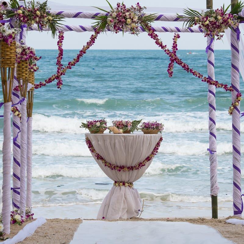 Huwelijksboog met bloemen op tropisch zandstrand wordt verfraaid, de openluchtopstelling die van het strandhuwelijk stock fotografie