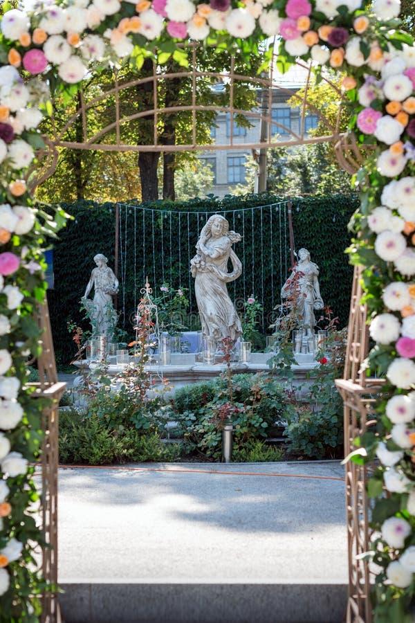 Huwelijksboog met bloemen in openlucht Mooie huwelijksopstelling Huwelijksceremonie in de tuin met beeldhouwwerken en royalty-vrije stock foto