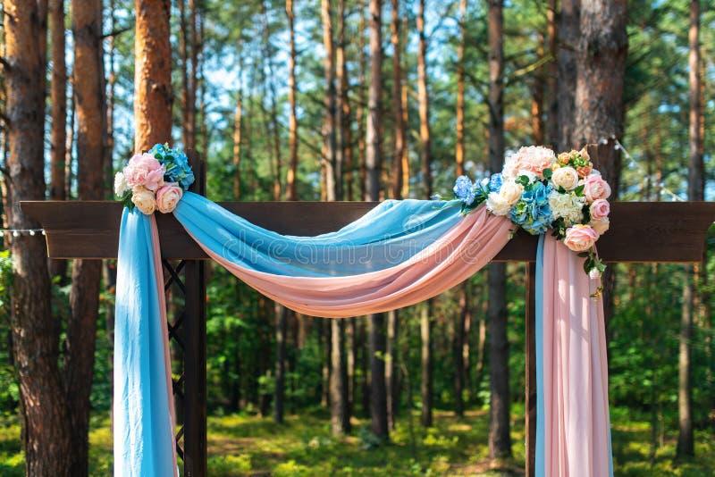 Huwelijksboog met bloemen in openlucht wordt verfraaid die Mooie huwelijksopstelling stock fotografie