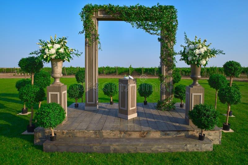 Huwelijksboog met doek en bloemen in openlucht wordt verfraaid die Mooie huwelijksopstelling Huwelijksceremonie op groen gazon in royalty-vrije stock afbeelding