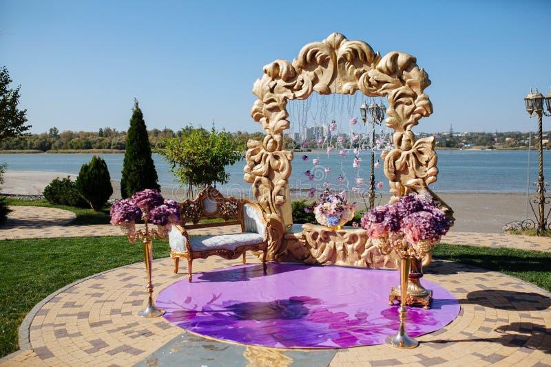 Huwelijksboog met gouden luxekader en purpere bloem en stoel op rivieroever Bruid en bruidegomceremonie stock afbeelding