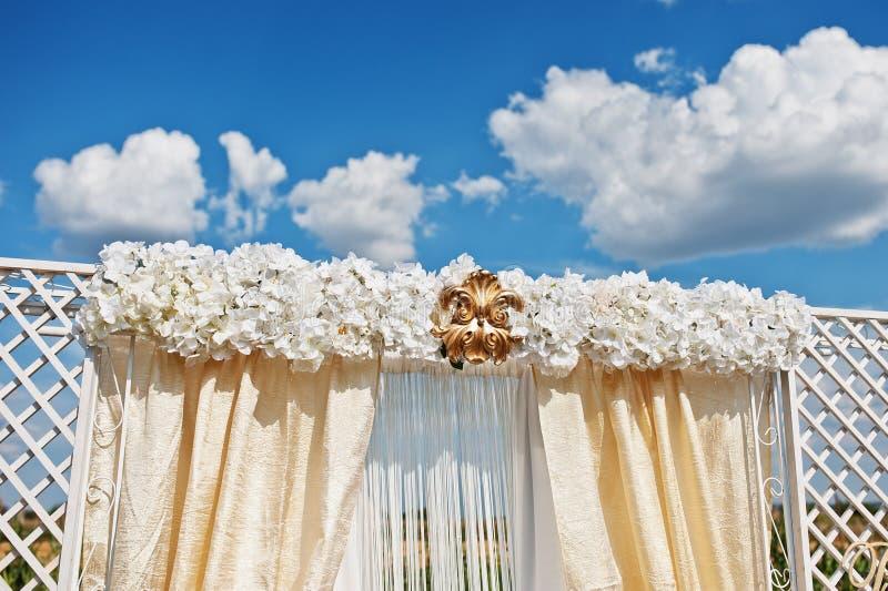 Huwelijksboog met witte bloemen en gouden ornament tegen blauw stock afbeeldingen