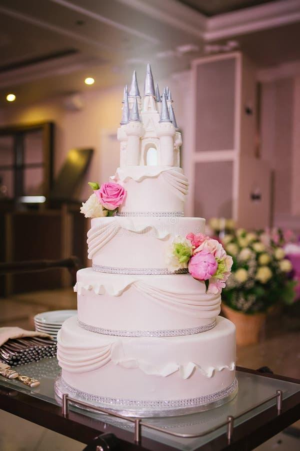Huwelijkscake die met bloemen en een kasteel wordt verfraaid royalty-vrije stock afbeelding