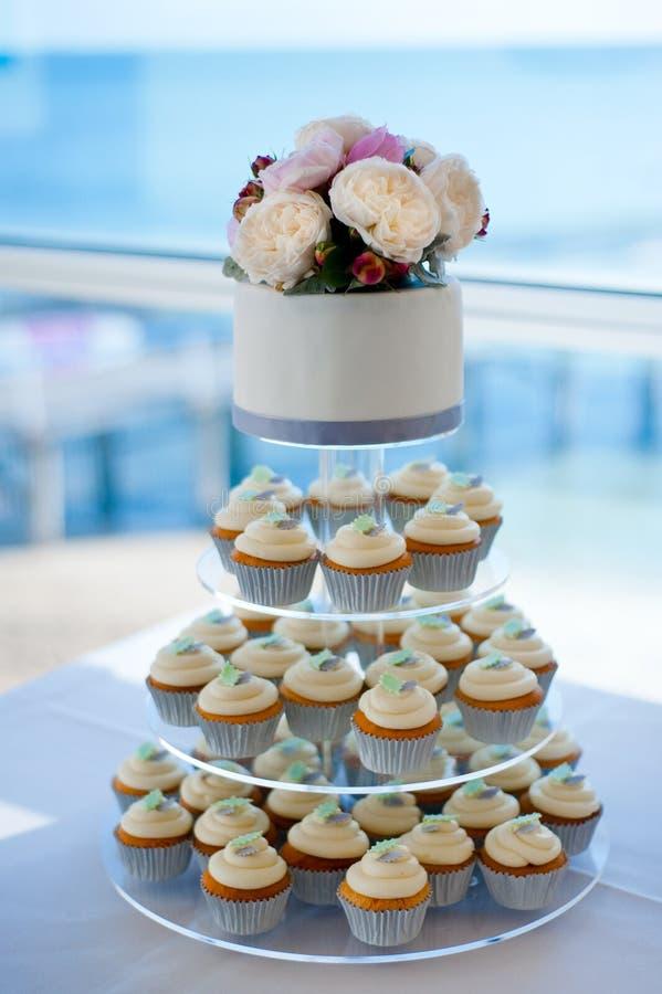 Huwelijkscake met cupcakes en rozen stock foto