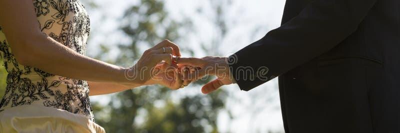 Huwelijksceremonie - close-upmening van een bruid die een ring plaatsen op haar royalty-vrije stock foto