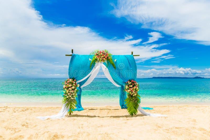 Huwelijksceremonie op een tropisch strand in blauw Boog verfraaid verstand royalty-vrije stock fotografie