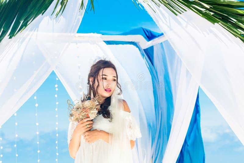 Huwelijksceremonie op een tropisch strand in blauw Gelukkige bruid met a stock afbeeldingen