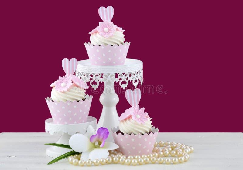 Huwelijksconcept cupcakes op marsalaachtergrond stock afbeelding