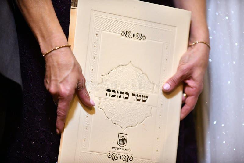 Huwelijkscontract in de handen van de moeder van de bruid bij een traditionele Joodse huwelijks Hebreeuwse Inschrijving - 'Huweli stock foto
