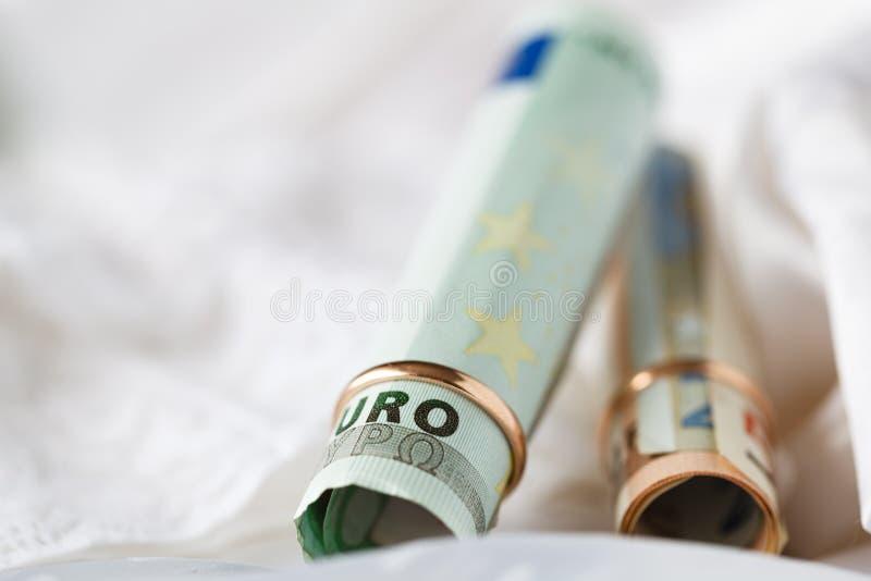 Huwelijkscontract Twee gouden trouwringen op het geld stock foto