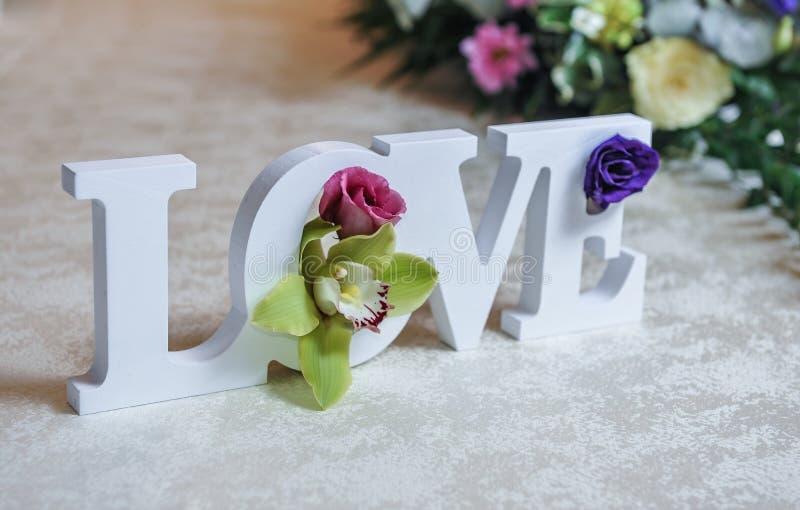 Huwelijksdecor, LIEFDEbrieven en bloemen op lijst Verse bloemen en LIEFDEdecoratie op feestelijke lijst Luxueuze huwelijksdecorat royalty-vrije stock afbeeldingen