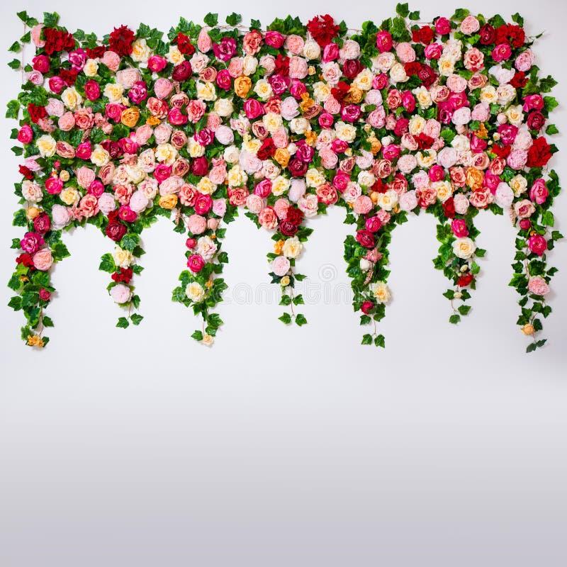 Huwelijksdecoratie - de samenstelling van kleurrijke rozen en pioenen bloeit over witte muur royalty-vrije stock foto's