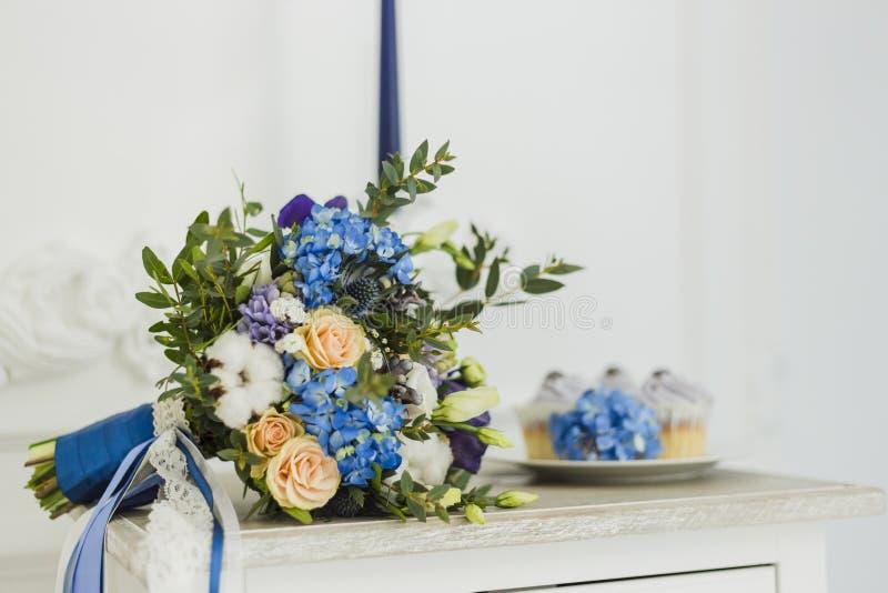 Huwelijksdecoratie met bride& x27; s boeket, kaars en cupcakes royalty-vrije stock foto's