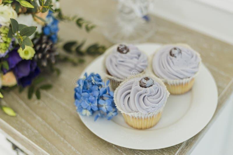 Huwelijksdecoratie met bride& x27; s boeket, kaars en cupcakes royalty-vrije stock foto