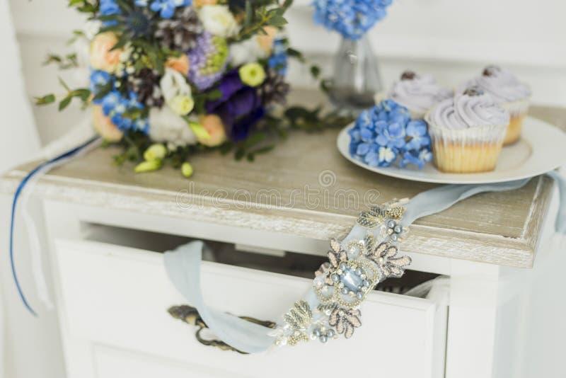 Huwelijksdecoratie met het boeket van de bruid, kaars en cupcakes stock afbeeldingen