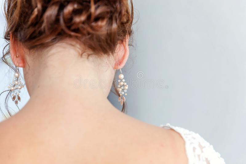 Huwelijksdetails en toebehoren Bruid die pareloorring zetten stock fotografie