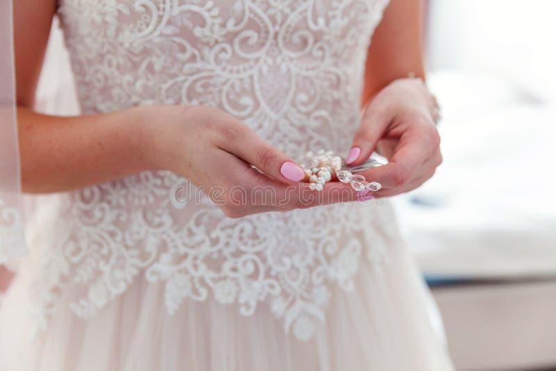 Huwelijksdetails en toebehoren Bruid die pareloorring zetten stock foto