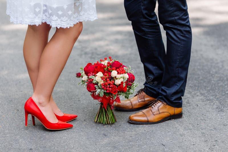 Huwelijksdetails: modieuze rode en bruine schoenen van bruid en bruidegom Boeket van rozen die zich op de grond tussen hen bevind stock afbeelding