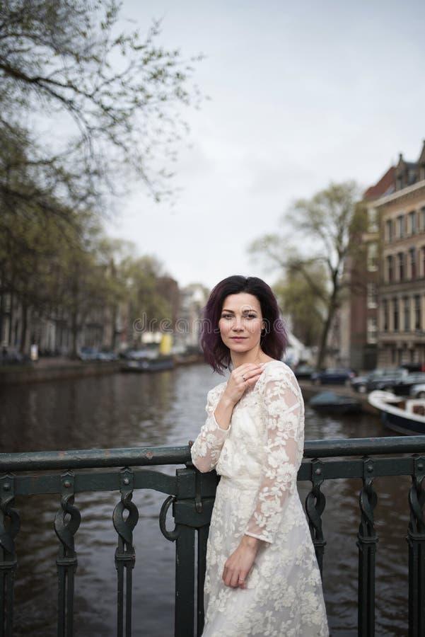 Huwelijksfoto het schieten Bruid die in Amsterdam lopen Tribune op brug en omhelzing stock afbeelding